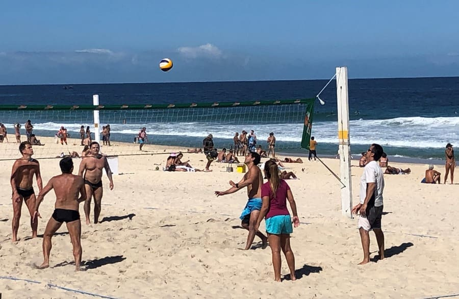 Friends playing sports at Ipanema Beach.